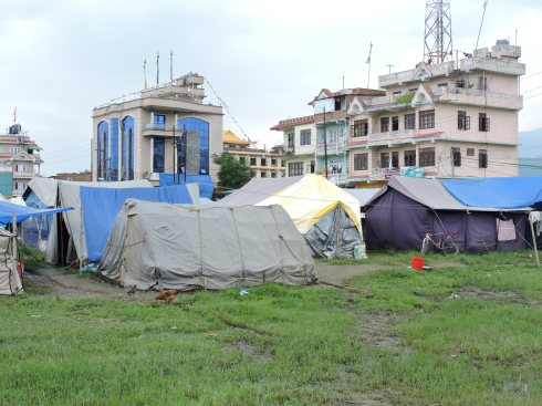 anonymous agglomeration of blue, grey and yellow tents on ever sodden ground