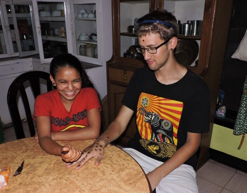 Januka applying Henna designs to one of the guests hands (face, ears)